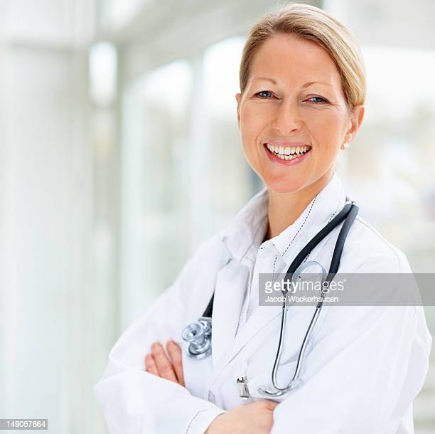 Smiling woman doctor closeup with arms crossed
