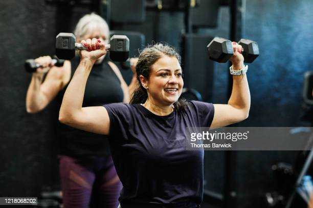 Smiling woman doing overhead dumbbell press during fitness class in gym