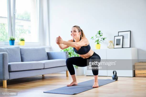 smiling woman doing squats during home workout - relaxation exercise stock pictures, royalty-free photos & images