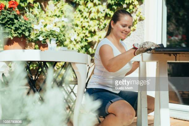 Smiling woman doing upcycling with old table.