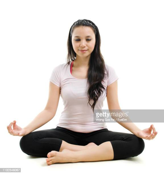 smiling woman doing yoga against white background - lotus position stock pictures, royalty-free photos & images
