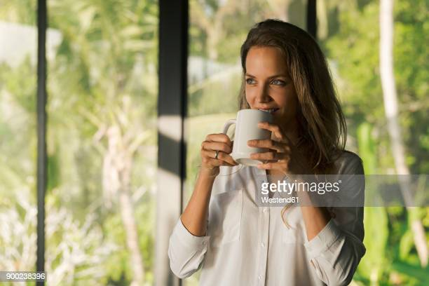 Smiling woman drinking coffee at home in front of lush tropical garden