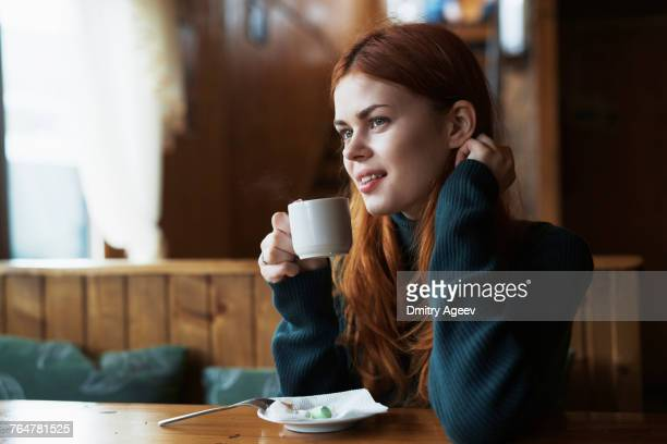 smiling woman drinking coffee in cafe - femme russe photos et images de collection