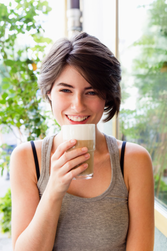 Smiling woman drinking coffee outdoors - gettyimageskorea