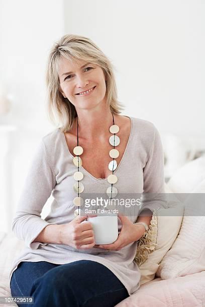 コーヒーを飲みながら微笑む女性