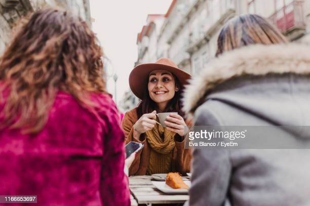 smiling woman drinking coffee while talking with friends in city - female friendship stock pictures, royalty-free photos & images