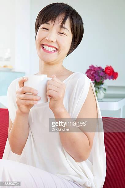 笑顔の女性がコーヒーを飲む