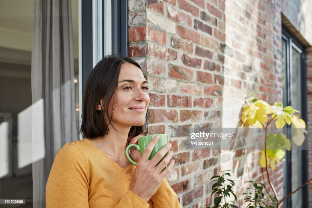 Smiling woman drinking from cup in front of her home : Stock-Foto