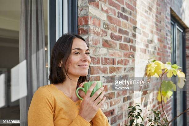 smiling woman drinking from cup in front of her home - bere foto e immagini stock