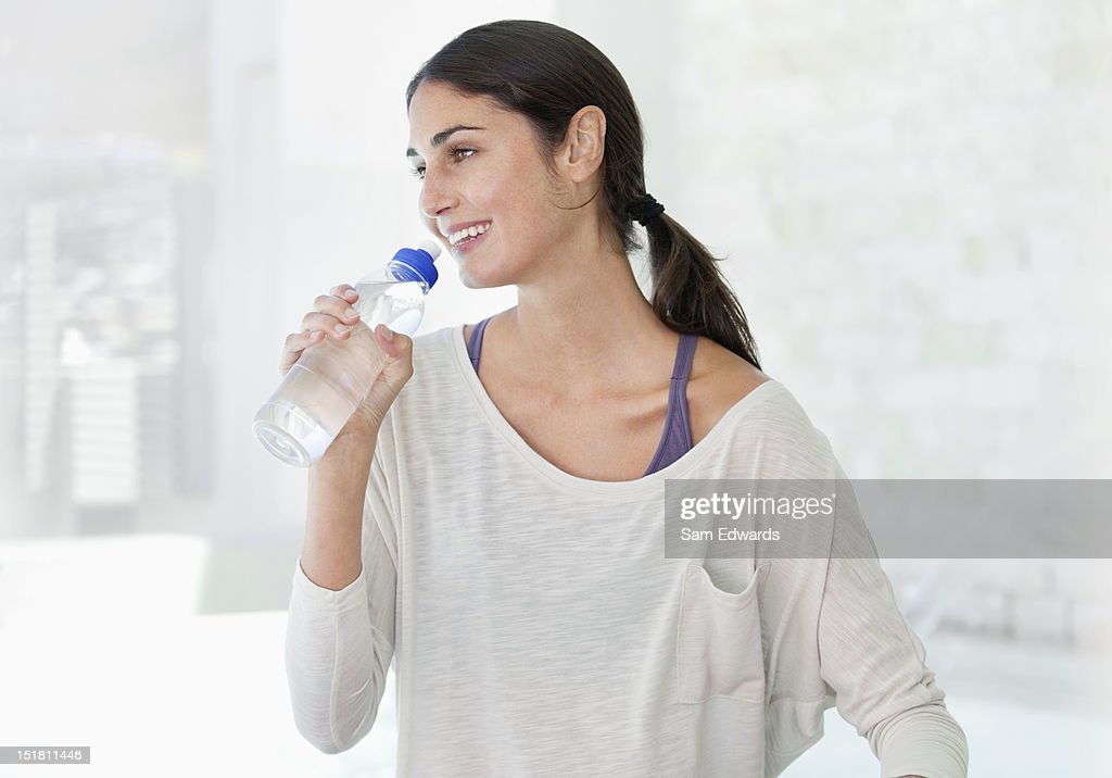 Smiling woman drinking from water bottle : Stock Photo