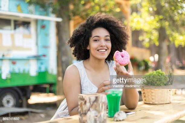 Femme souriante en anneau vert de cocktail et de manger à boire