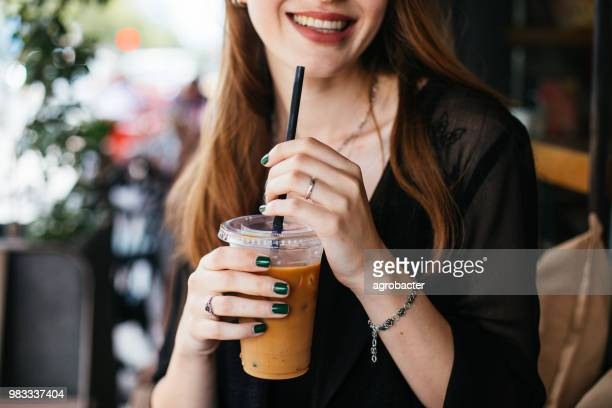 smiling woman drinking iced coffee - iced coffee stock pictures, royalty-free photos & images