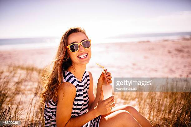 Smiling woman drinking lemonade at the beach