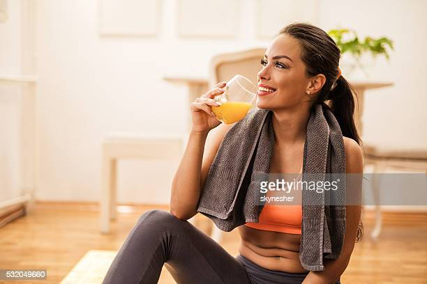 Smiling woman drinking orange juice after sports training.