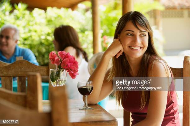 Smiling woman drinking red wine in cafe
