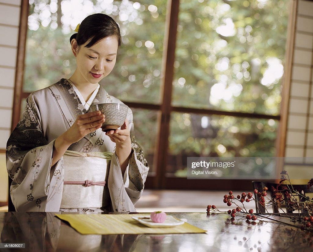 Smiling Woman Drinking Tea During a Japanese Tea Ceremony : Stock Photo
