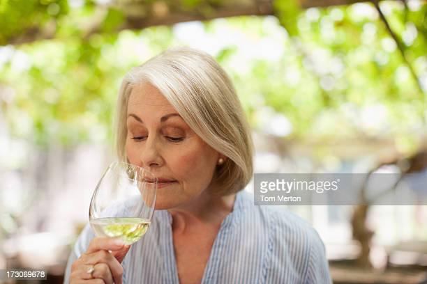 白ワインを飲みながら微笑む女性 - 年配の女性一人 ストックフォトと画像