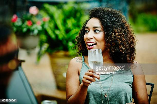 Smiling woman drinking wine with friends