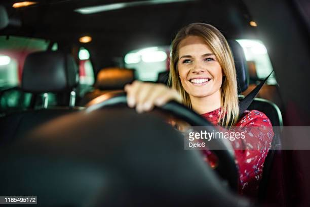 smiling woman driving a car in public garage. - driving stock pictures, royalty-free photos & images
