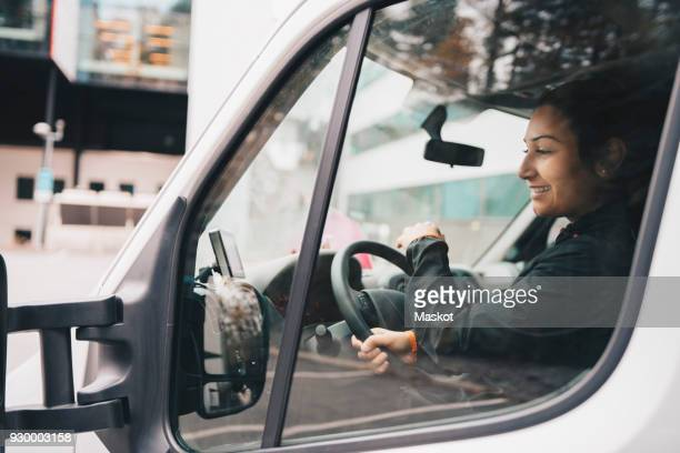 smiling woman driving delivery van in city - transportation stock pictures, royalty-free photos & images