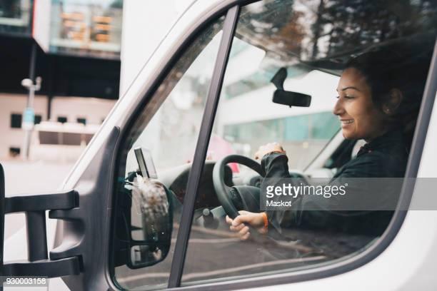smiling woman driving delivery van in city - transportmedel bildbanksfoton och bilder