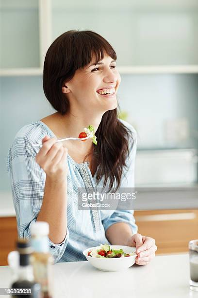 Smiling woman eating a bowl of salad at the table
