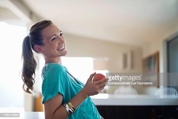 smiling woman eating apple in kitchen - paardenstaart haar naar achteren stockfoto's en -beelden