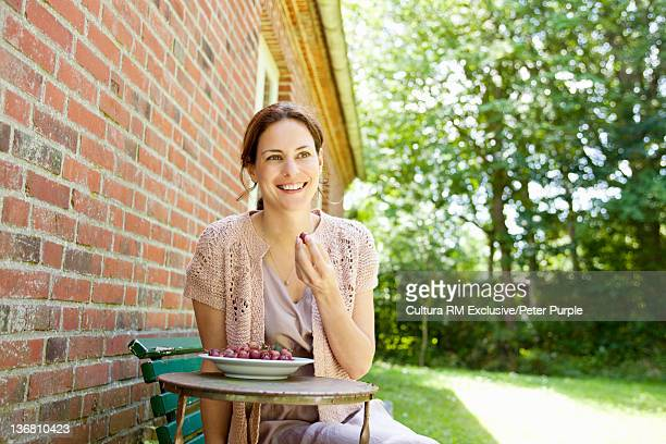 Smiling woman eating berries outdoors