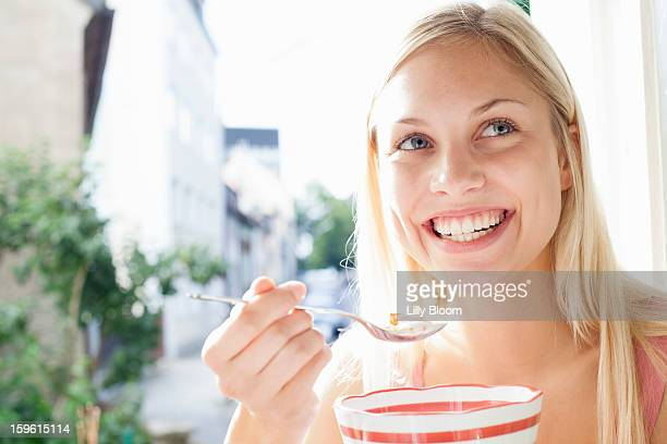 Smiling woman eating bowl of cereal