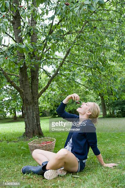 Smiling woman eating cherries outdoors