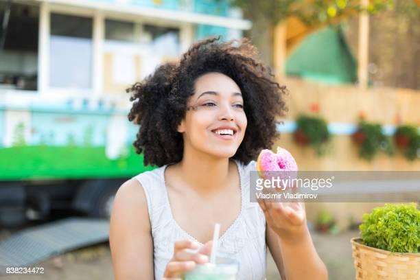 Smiling woman eating doughnut