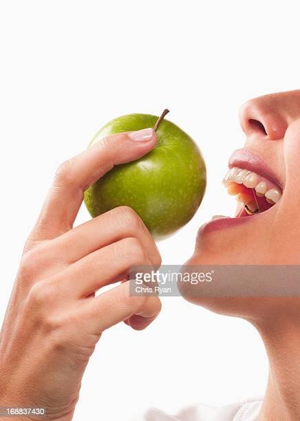 Smiling woman eating green apple