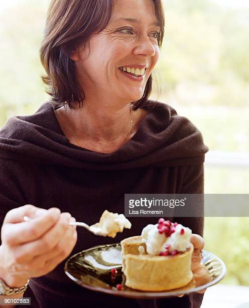 Smiling woman eating plate of dessert