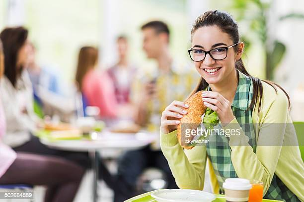 Smiling woman eating sandwich.