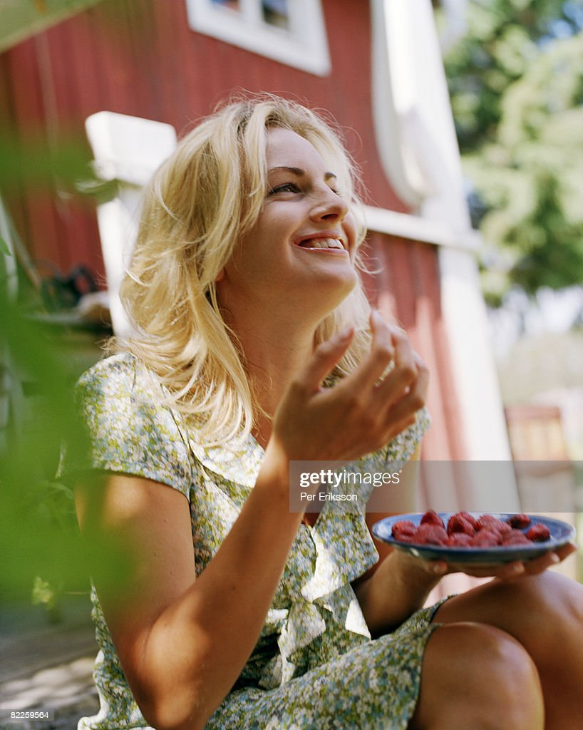 A smiling woman eating strawberries Sweden. : Stock Photo