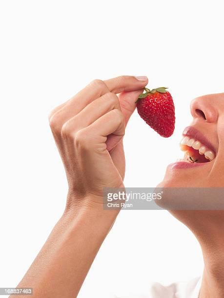 Sonriente mujer comiendo fresa
