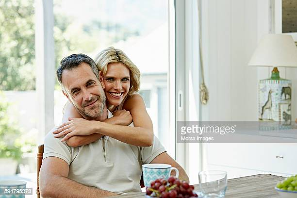 smiling woman embracing man at home - 40 44 jahre stock-fotos und bilder