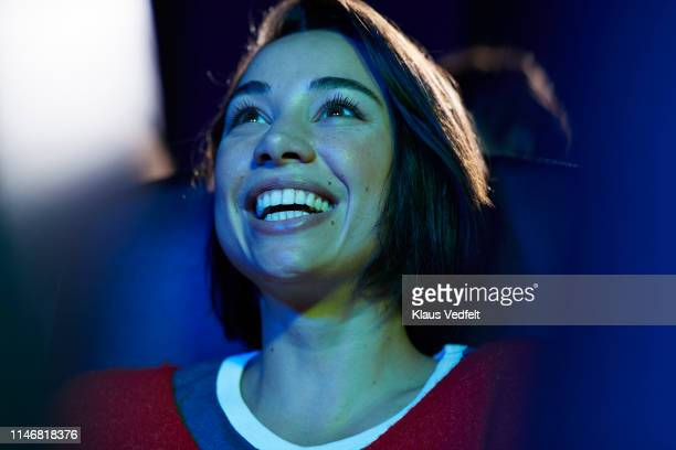 smiling woman enjoying at theater - arts culture and entertainment stock pictures, royalty-free photos & images