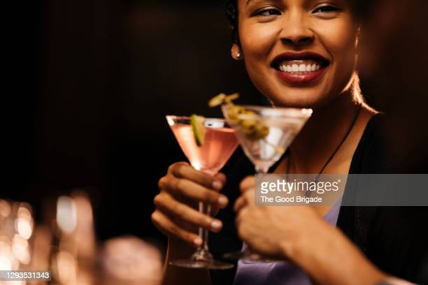 smiling woman enjoying cocktail with male friend at bar - cocktail party stock pictures, royalty-free photos & images