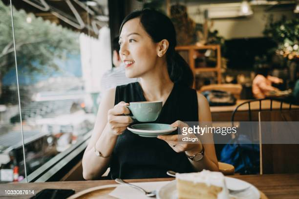 smiling woman enjoying coffee and looking through window in coffee shop - 東アジア ストックフォトと画像