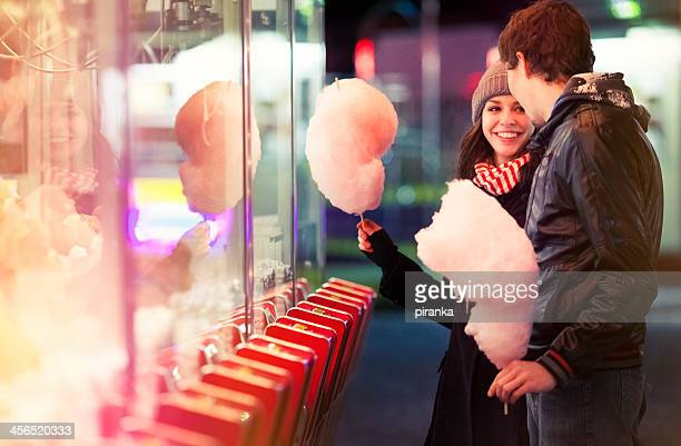 Smiling woman enjoying cotton candy with man