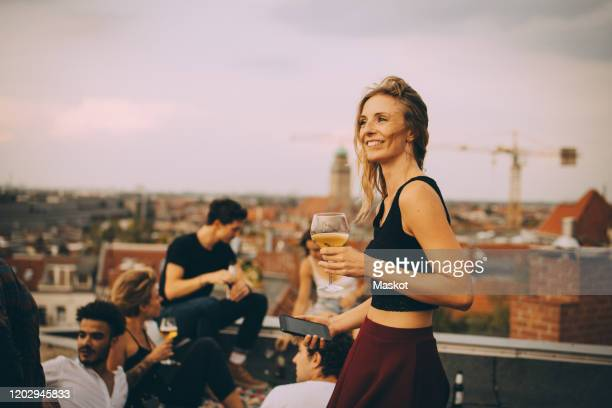 smiling woman enjoying drink while partying with friends at rooftop - roof stock pictures, royalty-free photos & images