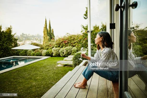 smiling woman enjoying glass of wine while watching sunset from backyard - doorway stock pictures, royalty-free photos & images