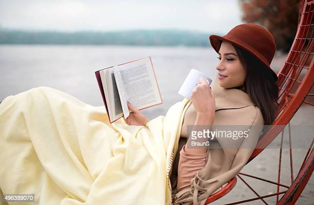 Smiling woman enjoying in a book and hot drink outdoors.