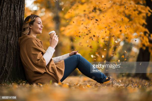 Smiling woman enjoying in coffee at the park.