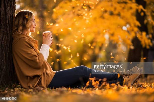 Lächelnde Frau in Tasse Kaffee im Herbst Park genießen.