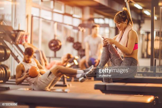 Smiling woman enjoying in music over earphones in a gym.