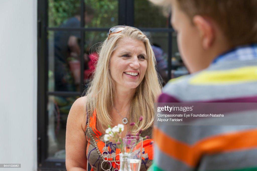 Smiling woman enjoying lunch on garden patio : Stock Photo