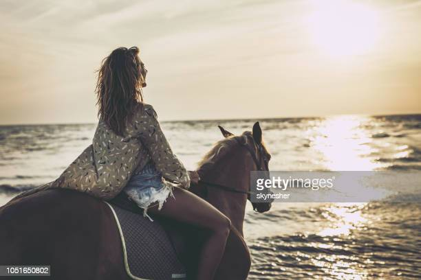 Smiling woman enjoying on her horse at the beach.