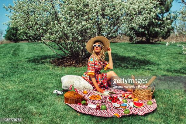 smiling woman enjoying picnic on field at park - picnic stock pictures, royalty-free photos & images
